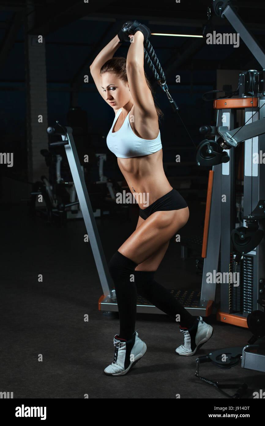 Mujer levantando pesas en una máquina para culturistas. Ella tiene un hermoso cuerpo con grandes músculos. Imagen De Stock
