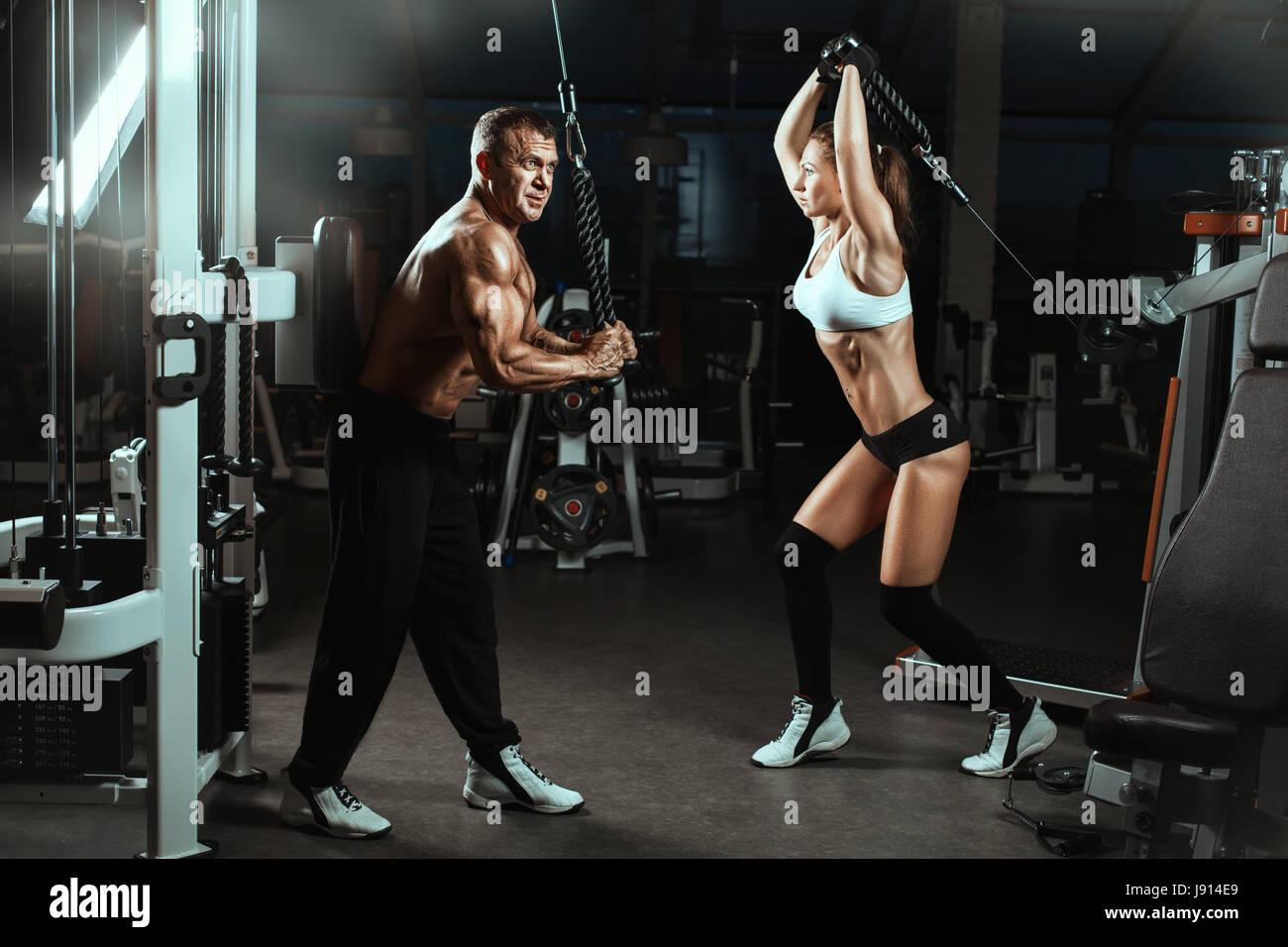 Hombre y mujer entrenados músculos en el gimnasio. Se entrenan con máquinas para culturistas. Imagen De Stock