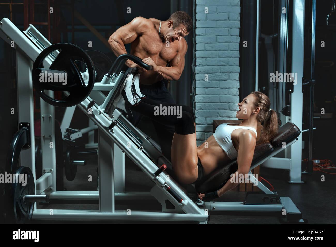 Hombre culturista capacita a las mujeres. Mujer en la máquina gire los músculos de la pierna. Imagen De Stock