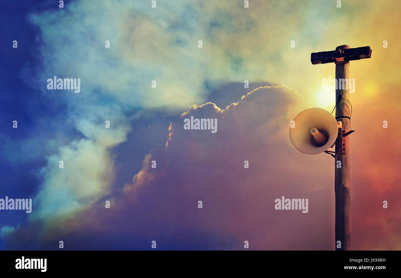 Altavoz exterior Sistema de advertencia sobre el poste de telégrafo contra un fondo de cielo lleno de humo. Imagen De Stock