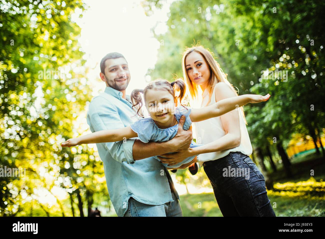Familia feliz con un hijo divirtiéndonos juntos en verano del parque de la ciudad Imagen De Stock