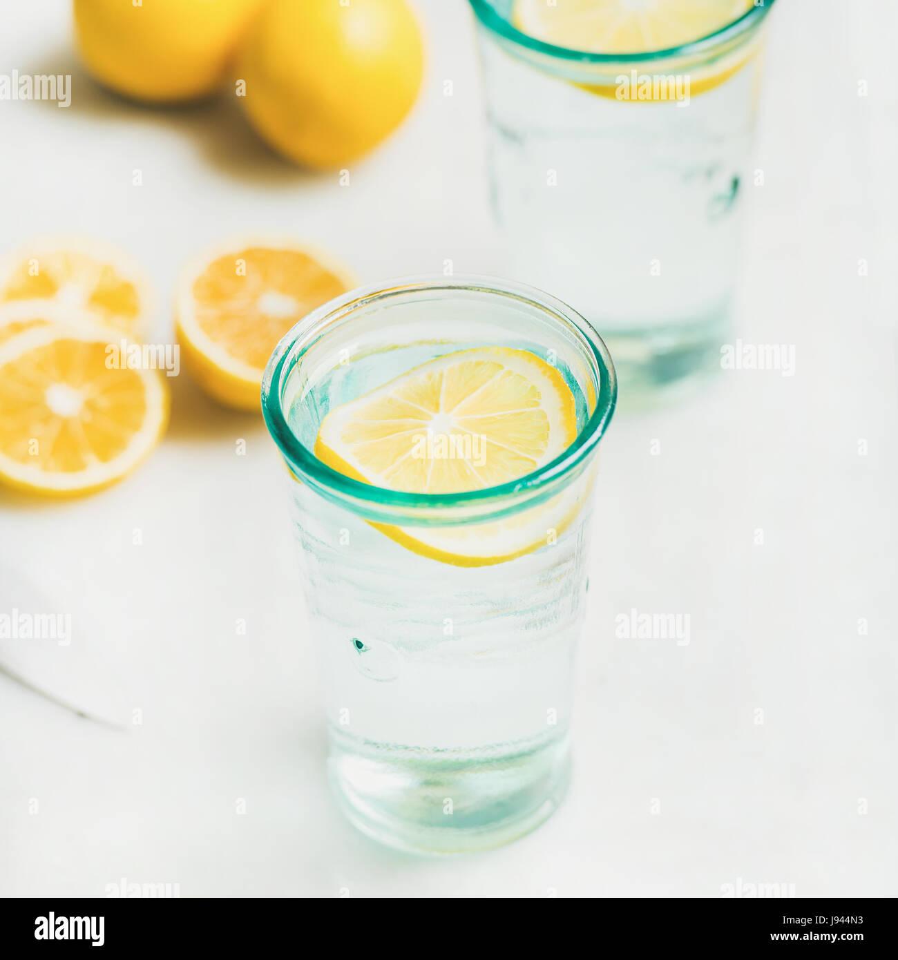 Mañana detox agua de limón en copas sirve con limones frescos Foto de stock