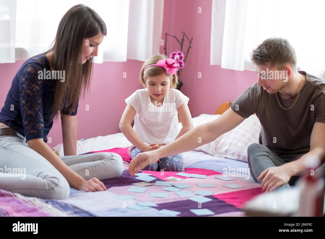 Madre e hija jugando en la cama. Concepto de diversión familiar Imagen De Stock
