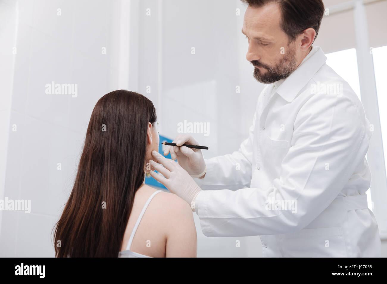 Diligente consciente cirujano plástico aplicando directrices precisas Imagen De Stock