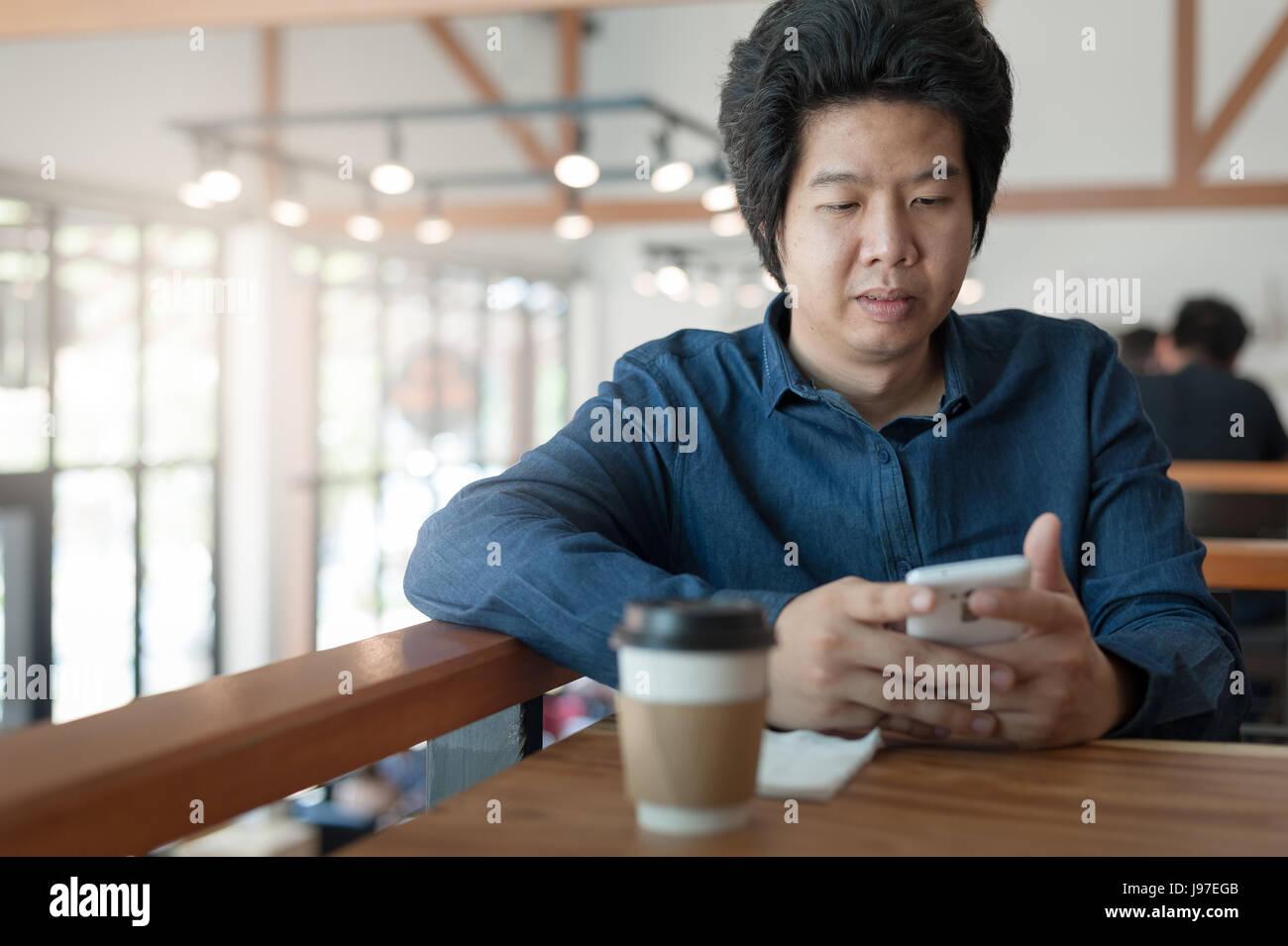 Empresario freelance asiáticos adultos mediante smartphone para la red social mientras está sentado en Imagen De Stock