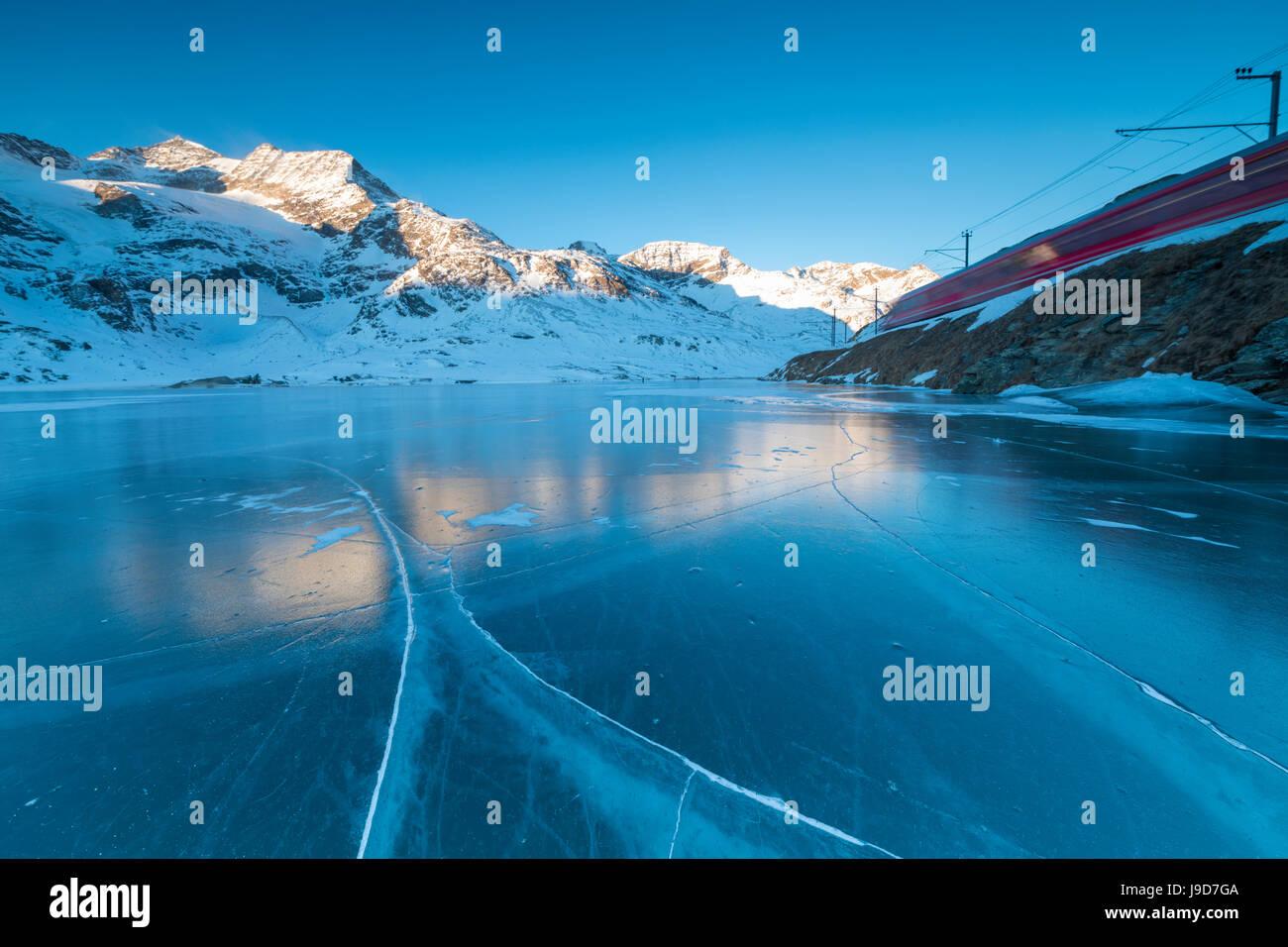 El Bernina Express tren funciona junto al lago congelado Bianco, Bernina Pass, cantón de Graubunden, Engadin, Imagen De Stock