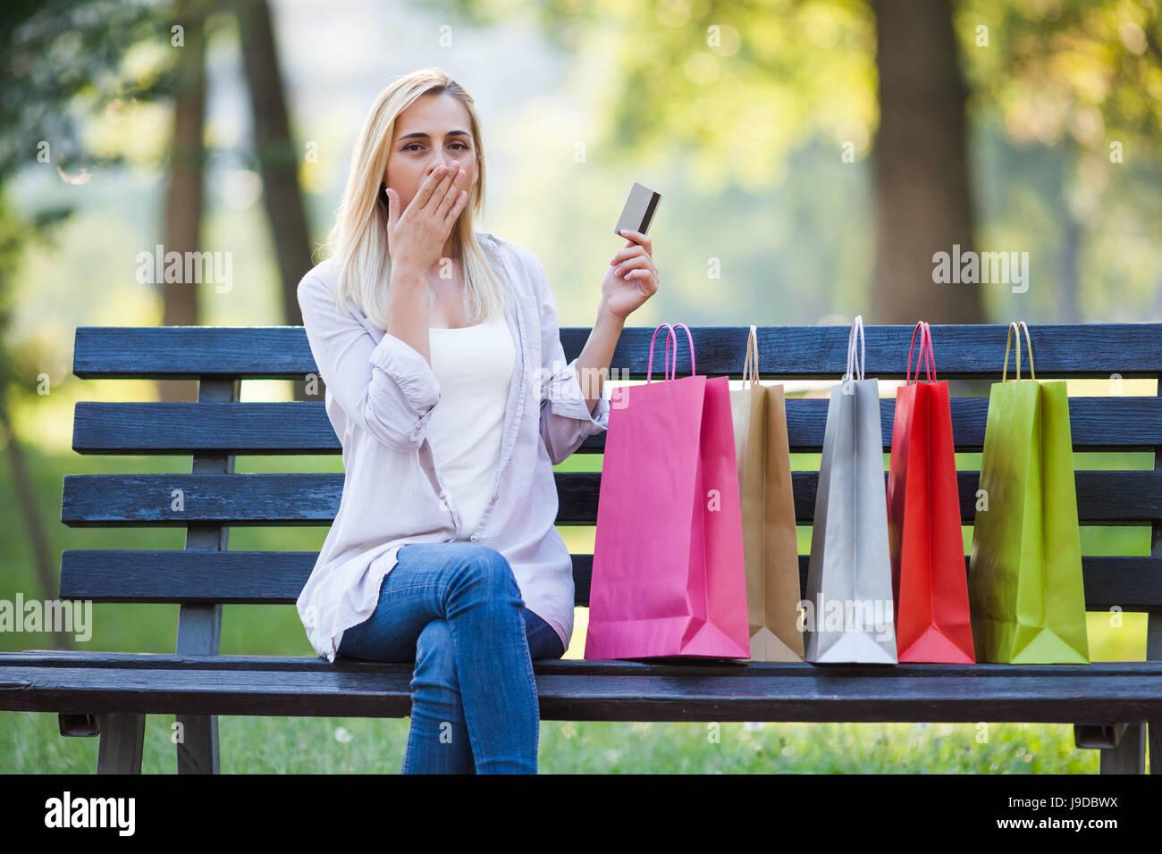 Mujer joven está sentado en el parque después de ir de compras. Ella está nerviosa porque ha gastado Imagen De Stock