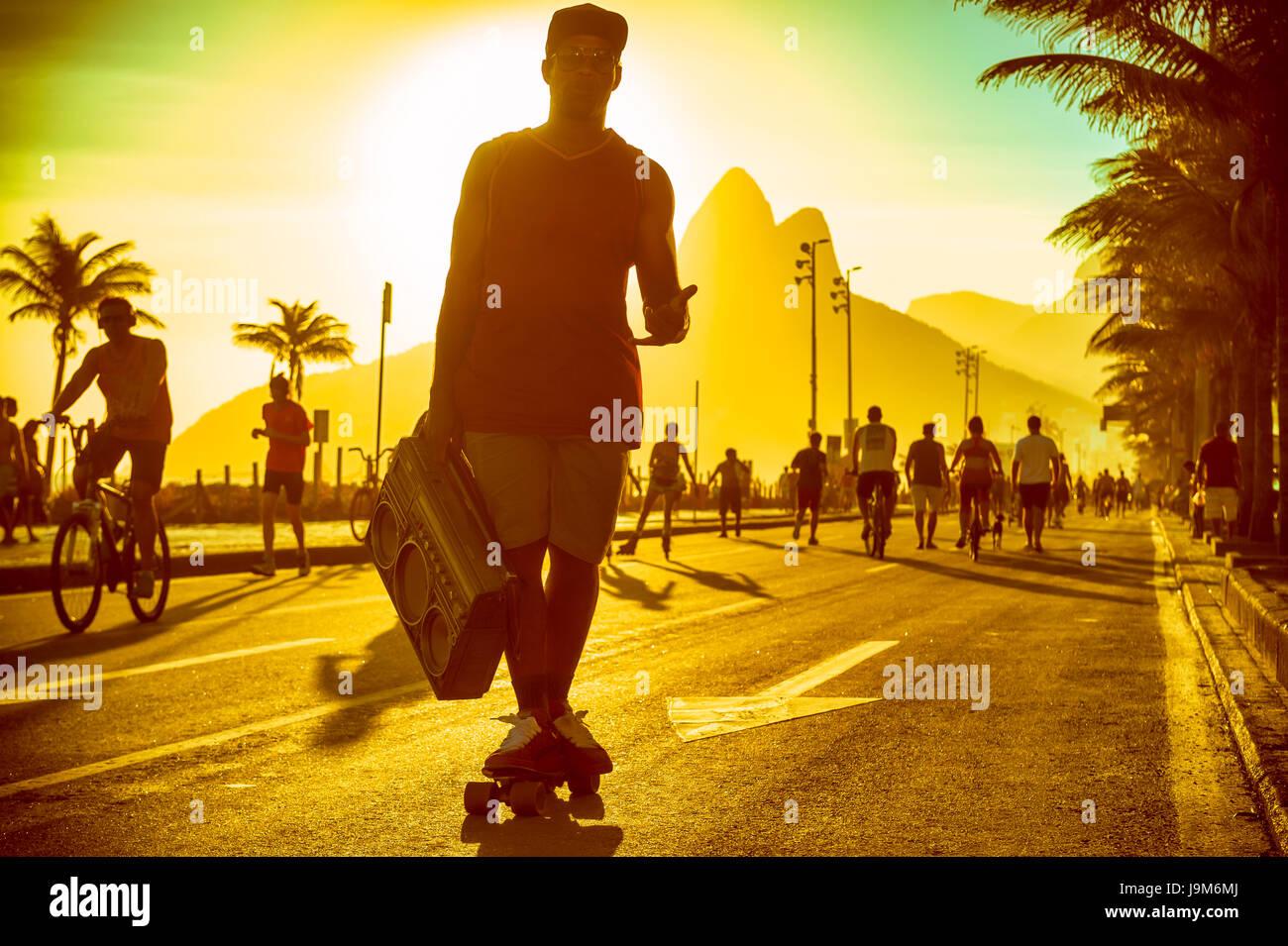Silueta de hombre brasileño patinar con boombox en la playa de Ipanema en Rio de Janeiro, Brasil Foto de stock