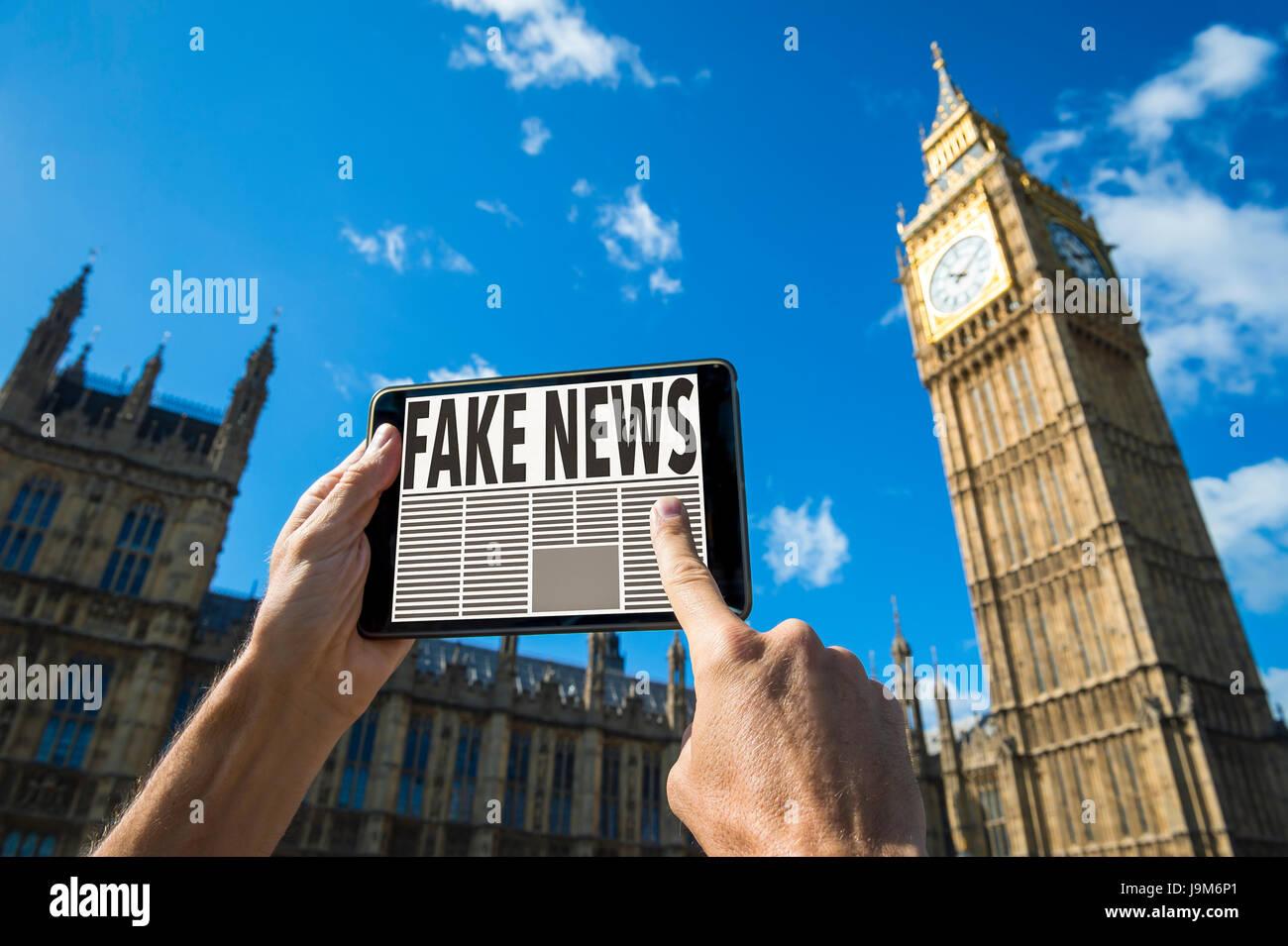 Desplazamiento a través de lector de noticias falsas historias sobre su tablet pc en frente de las Casas del Imagen De Stock