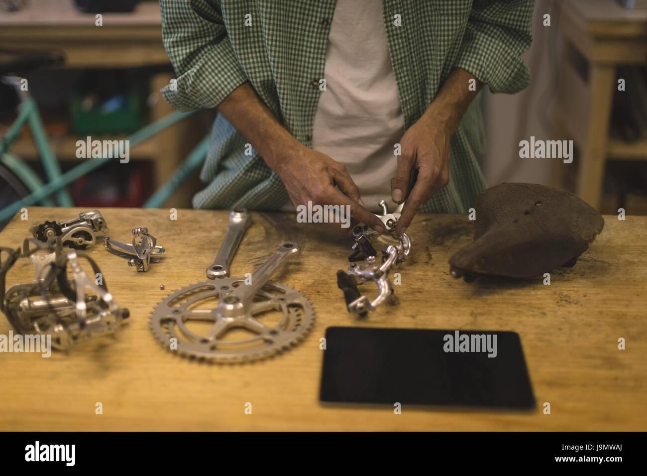 La sección central de trabajadores reparando bicicletas en la pieza en la mesa taller de reparación Imagen De Stock
