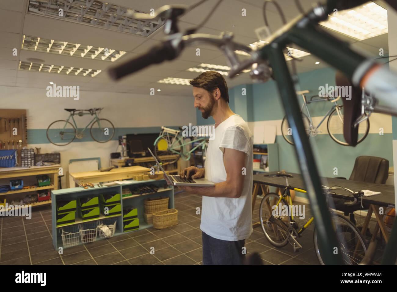 Vista lateral del empleado mediante el portátil mientras está parado en el taller de bicicletas Imagen De Stock