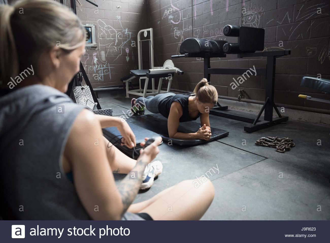 Entrenador personal femenino de distribución cliente haciendo ejercicio en el gimnasio del tablón áspero Imagen De Stock