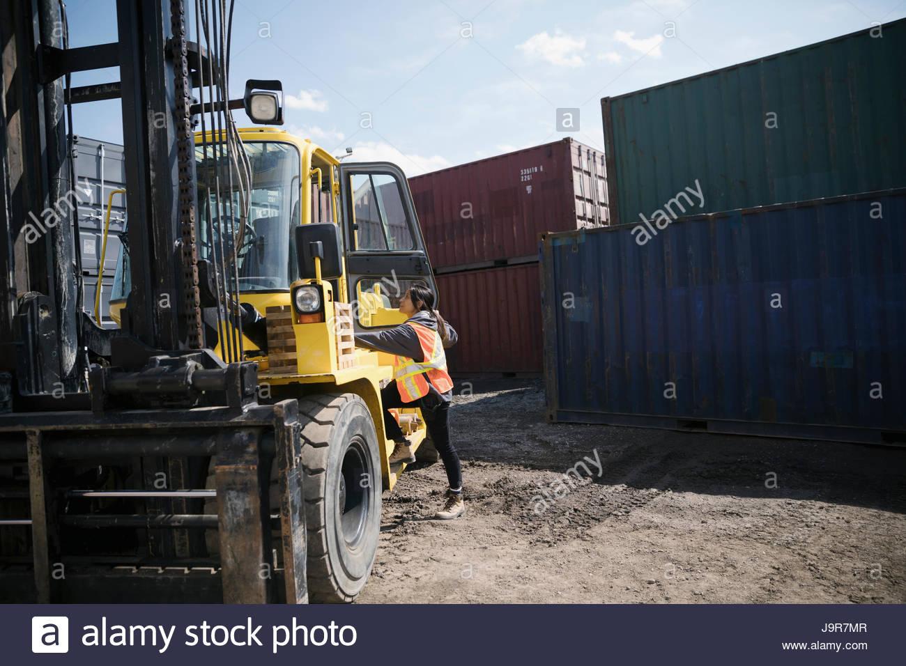 Conductor de carretilla elevadora femenino en el soleado patio de contenedores industriales Imagen De Stock