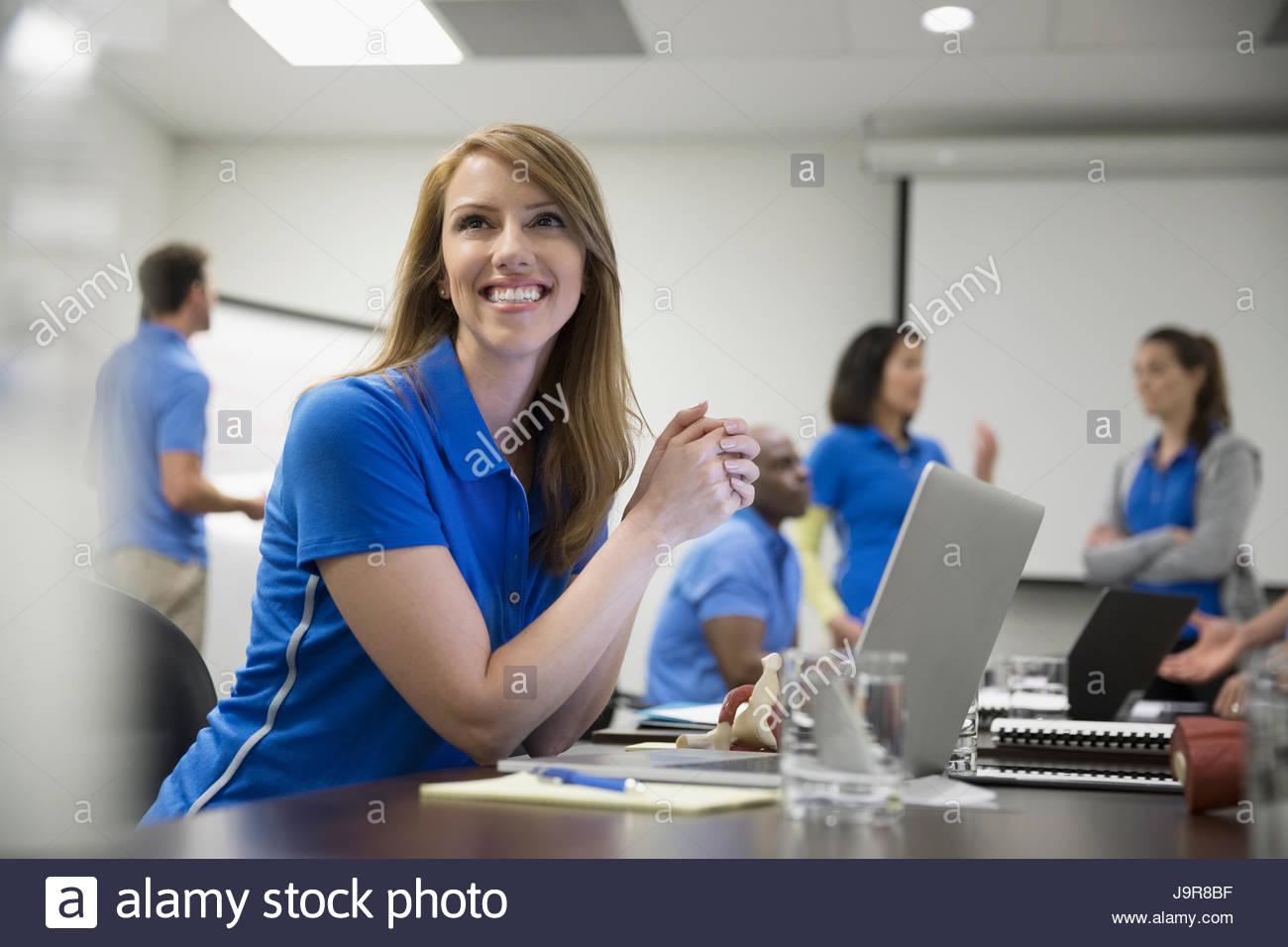 Sonriente femenino centrado fisioterapeuta con laptop en la sala de reunión de formación Imagen De Stock