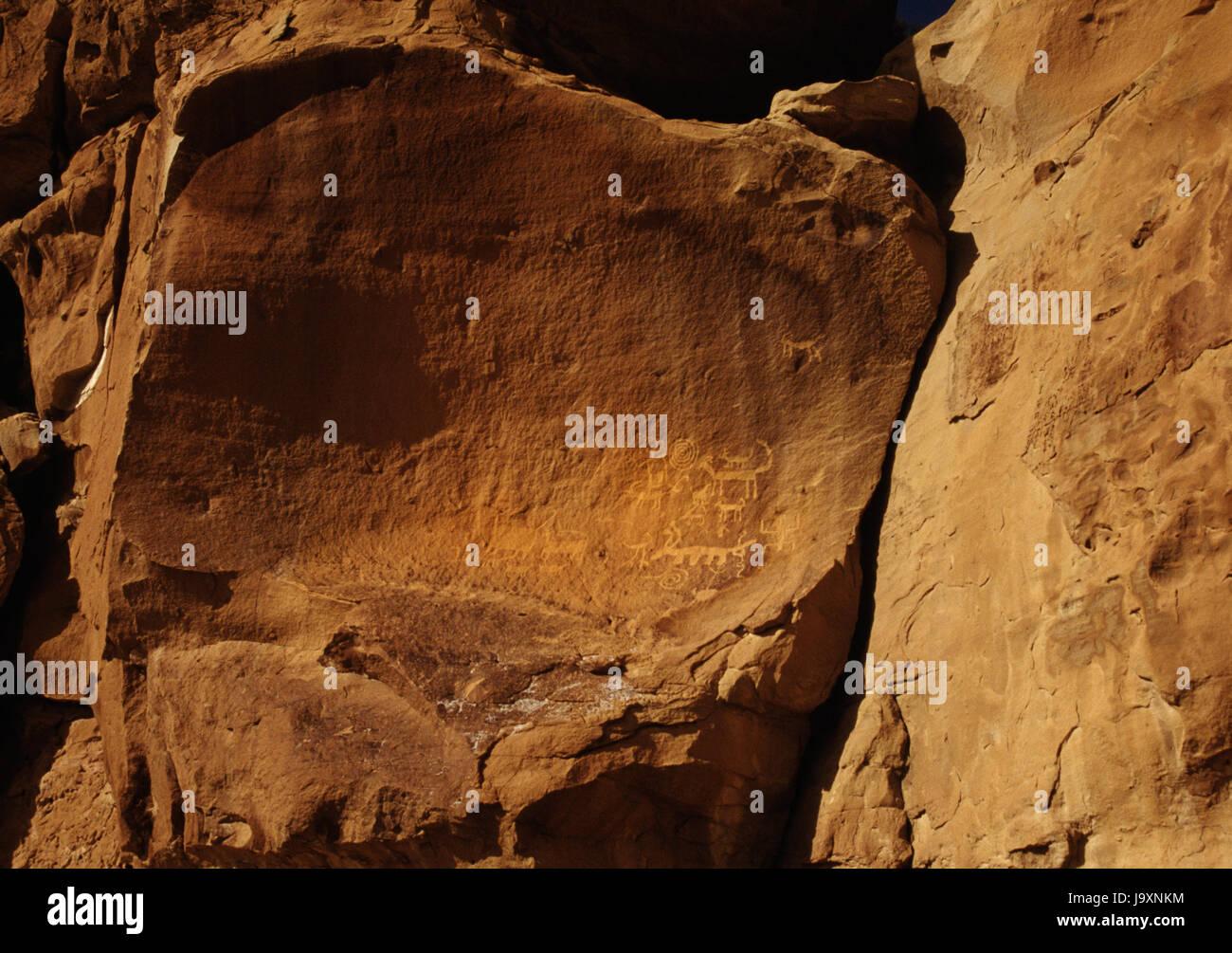 San Juan Anasazi tallados en la pared del cañón de piedra arenisca en una vida de pueblo, Cañón del Chaco, Nuevo México, EE.UU.: anthropomorph con espiral & horned cuadrúpedos. Foto de stock