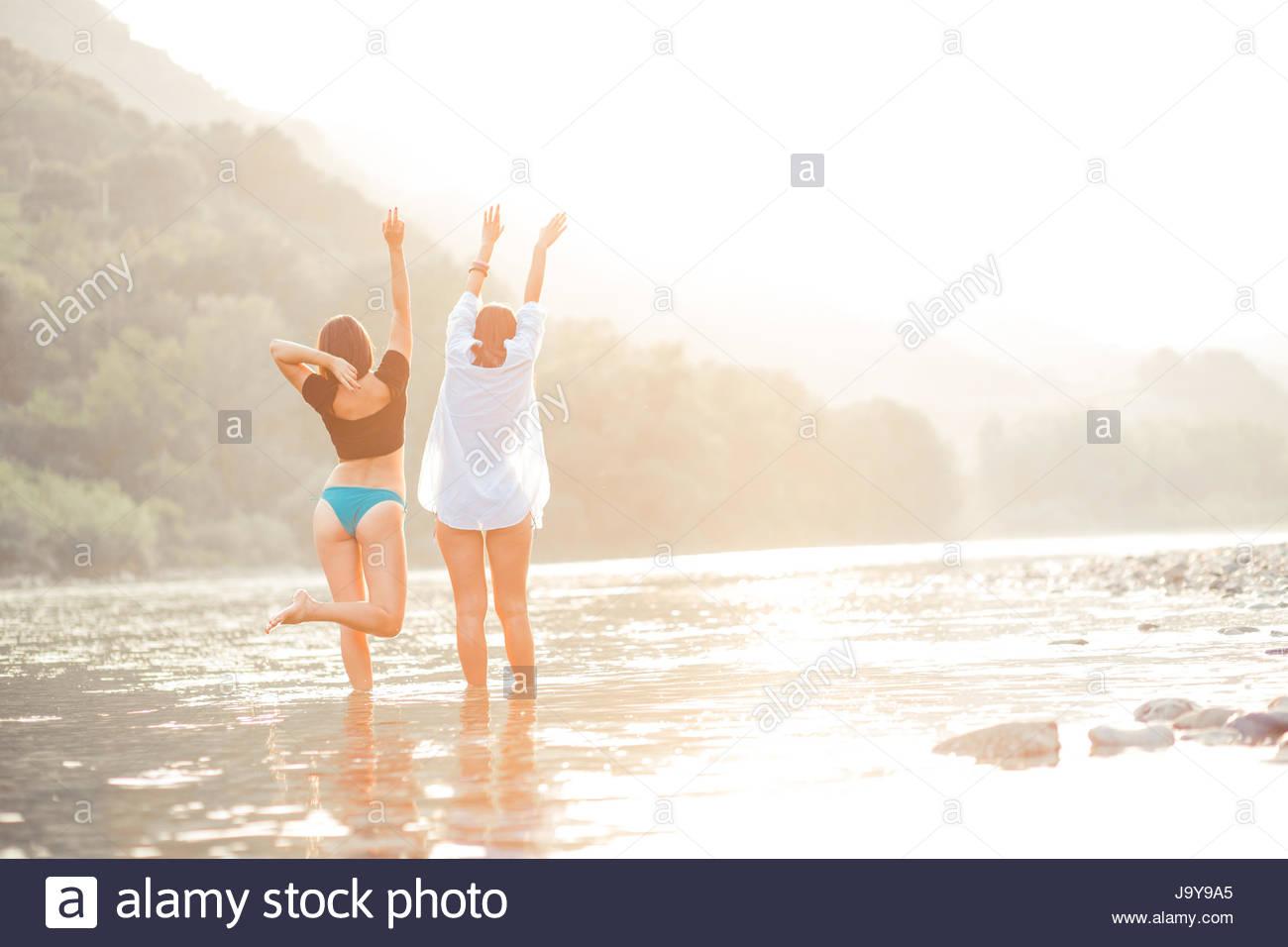 Las mujeres jóvenes en la playa en sunset tener buen tiempo Imagen De Stock