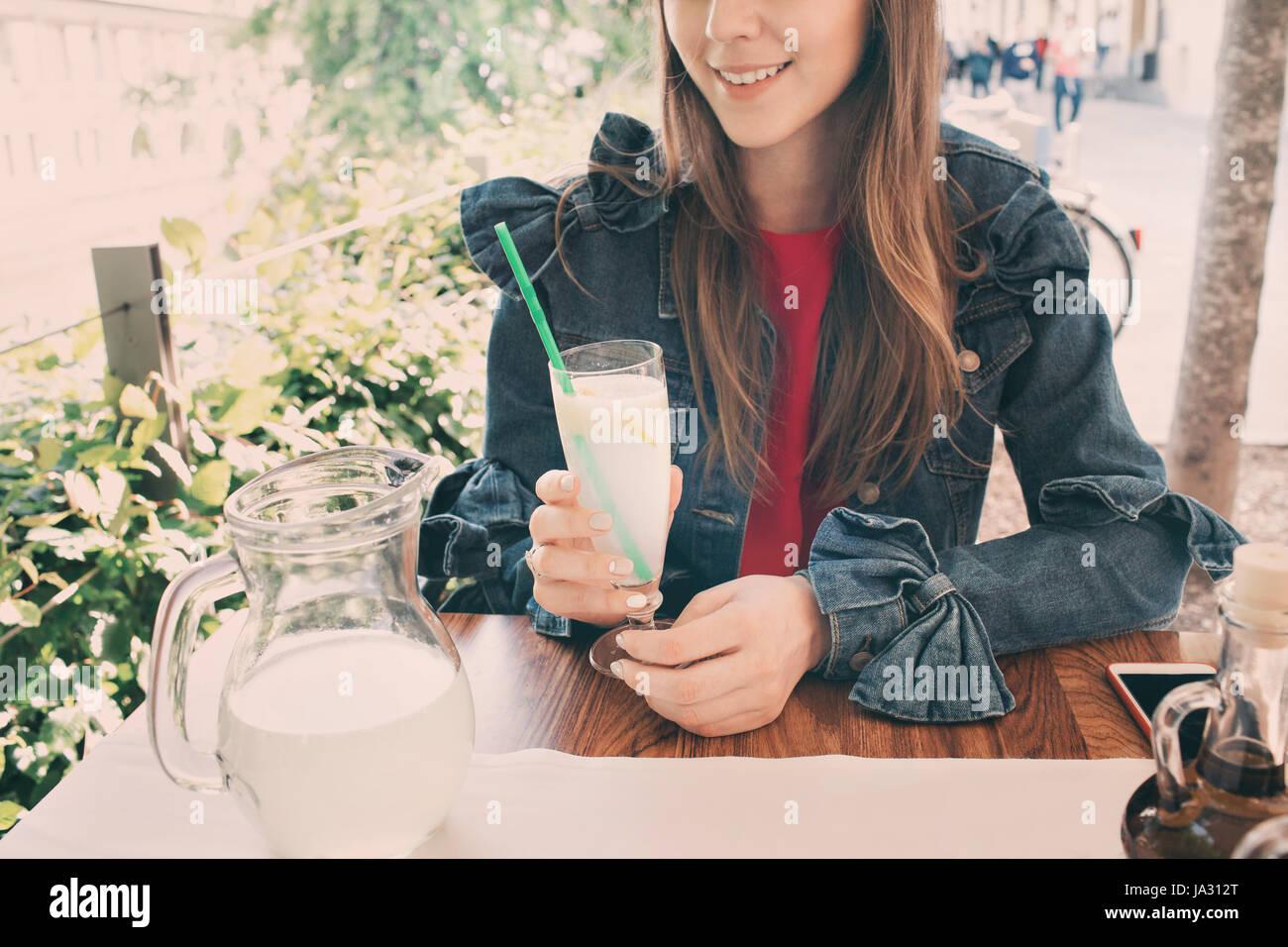 Chica sonriente joven bebiendo sabrosos cócteles dulces , increíble día de relax, deliciosa limonada, Imagen De Stock