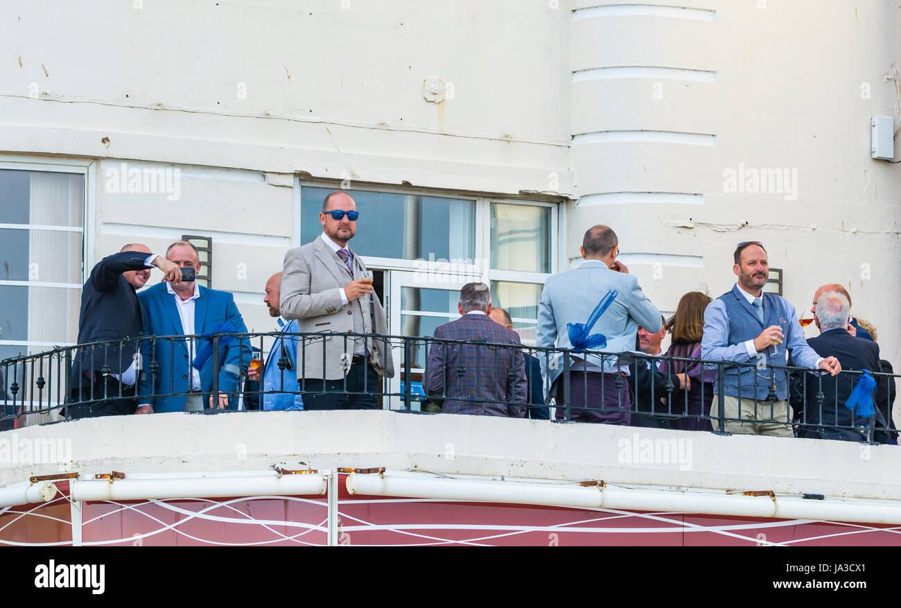Grupo de hombres de mediana edad de pie fuera en el balcón bebiendo. Imagen De Stock