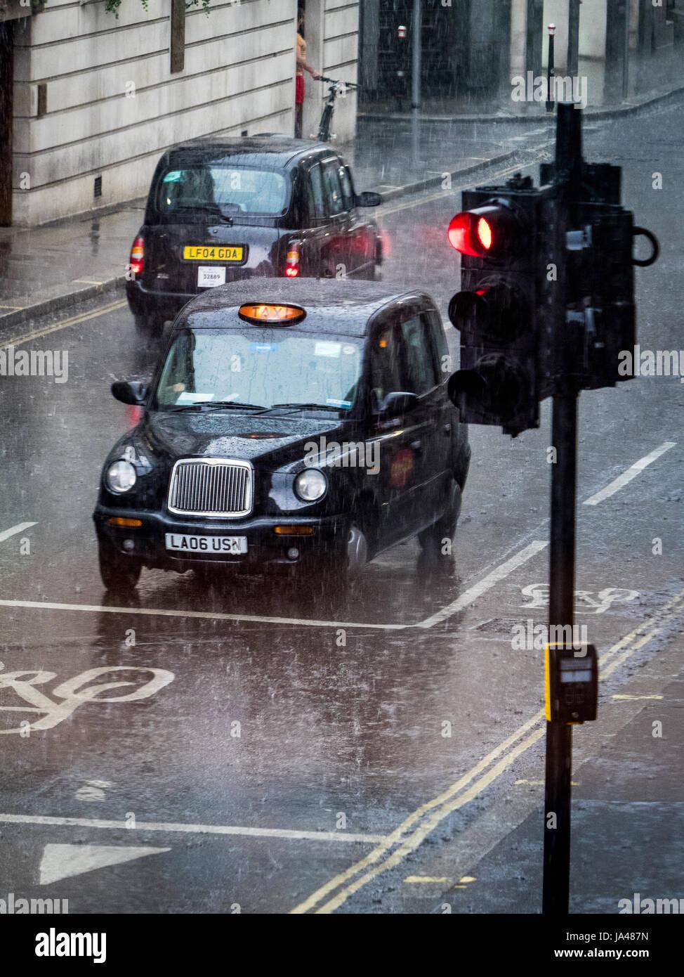 London taxi taxi negro se detiene en un semáforo en un chubasco Imagen De Stock