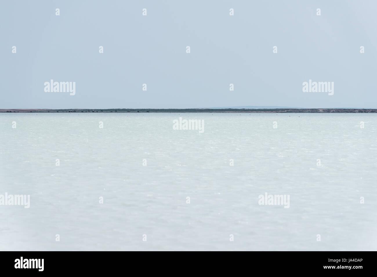 Una escena minimalista con un cielo despejado, agua azul y una línea de horizonte Imagen De Stock