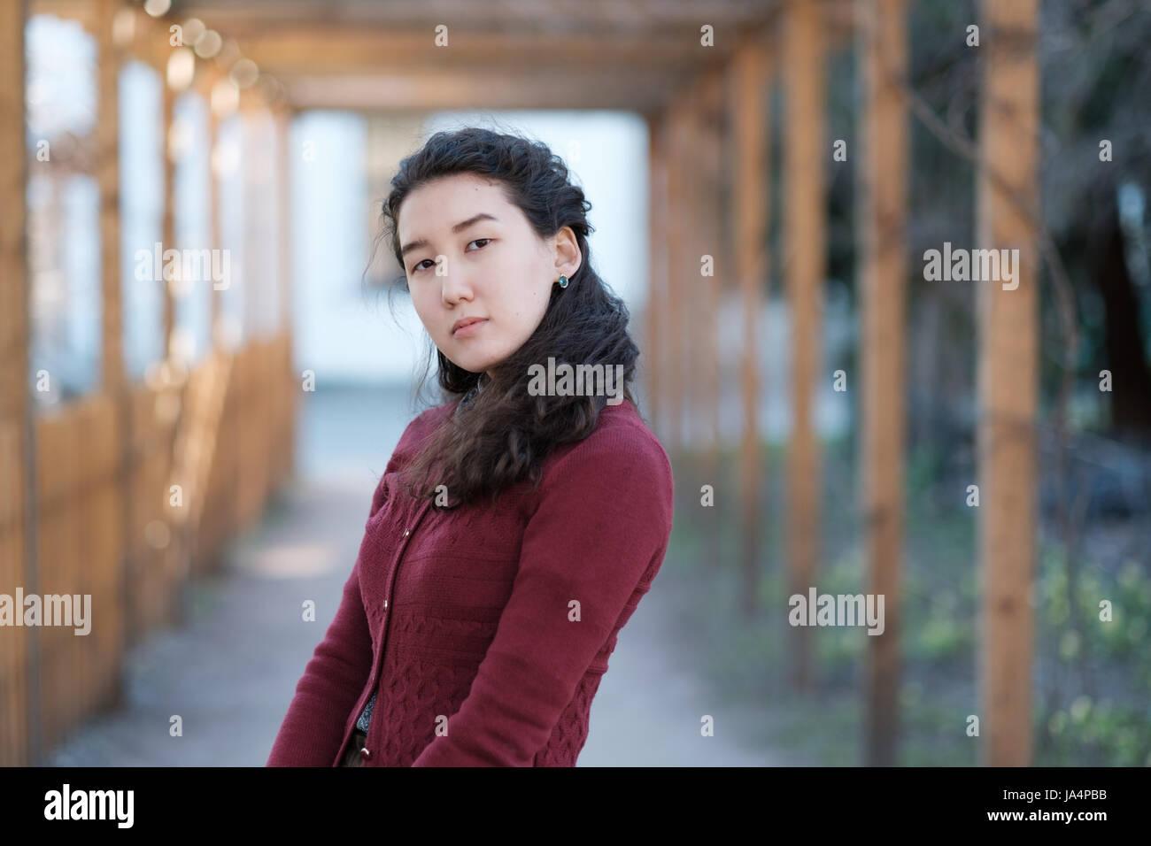 Una hermosa muchacha asiática está en modesta ropa en medio de un callejón en el parque Foto de stock