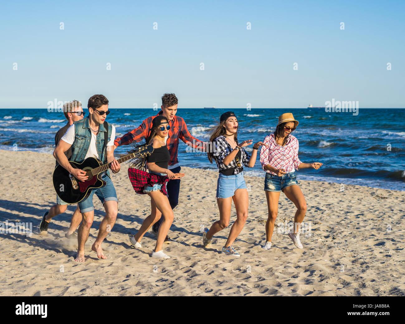 Fiesta en la playa con la guitarra. Amigos bailando juntos en la playa. Imagen De Stock