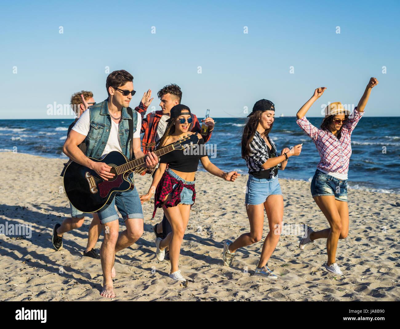 El hombre tocando la guitarra en la playa y sus amigos bailan alrededor de él Imagen De Stock