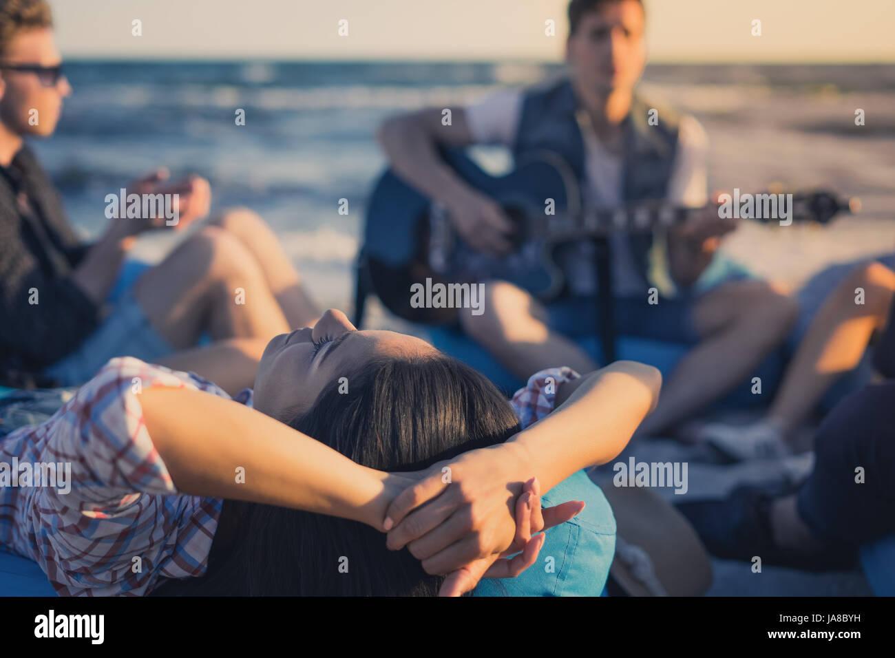 Grupo de amigos con la guitarra y el alcohol de la fiesta en la playa Foto de stock