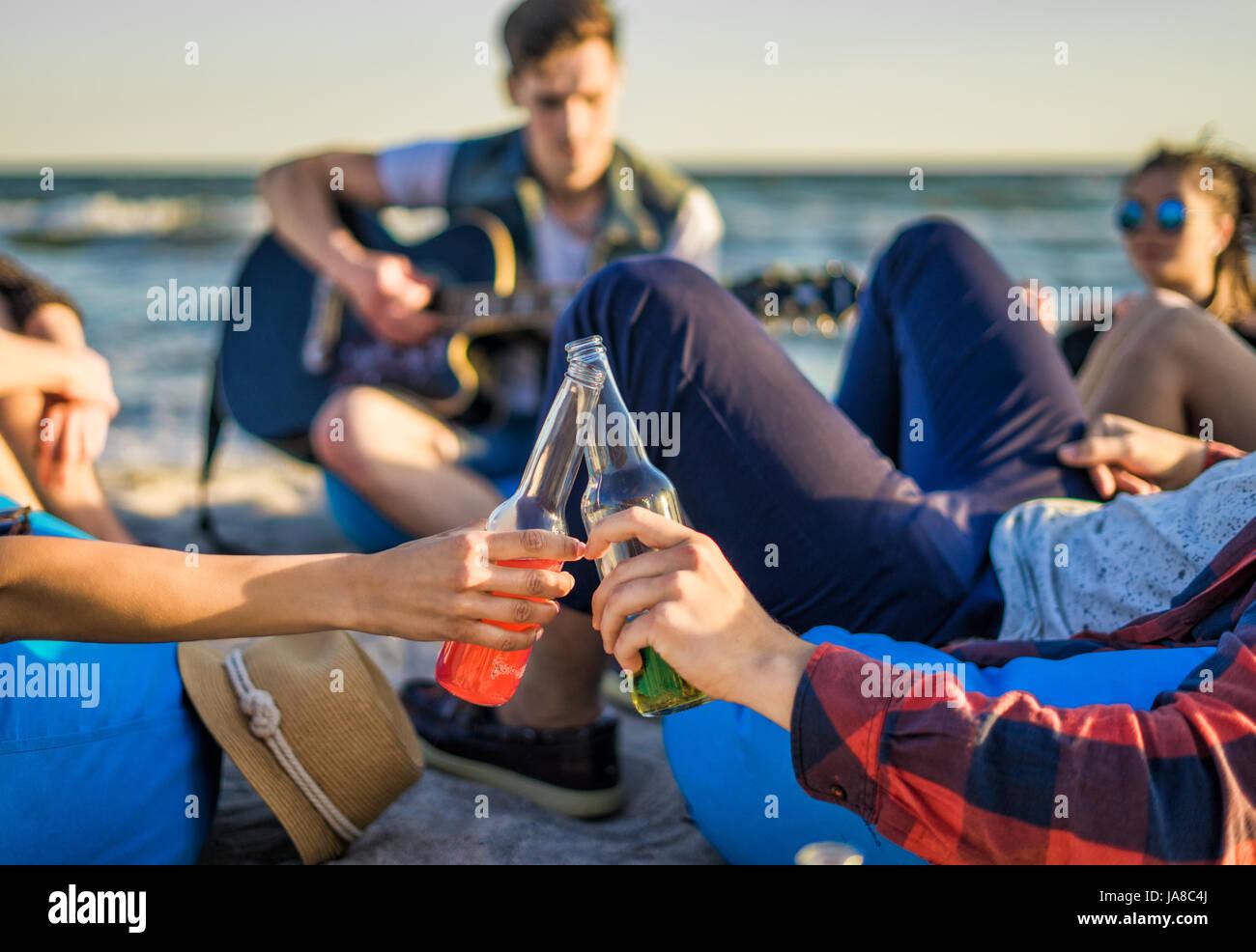 Acercamiento de manos vasos tintineo de botellas de cerveza en la playa Imagen De Stock