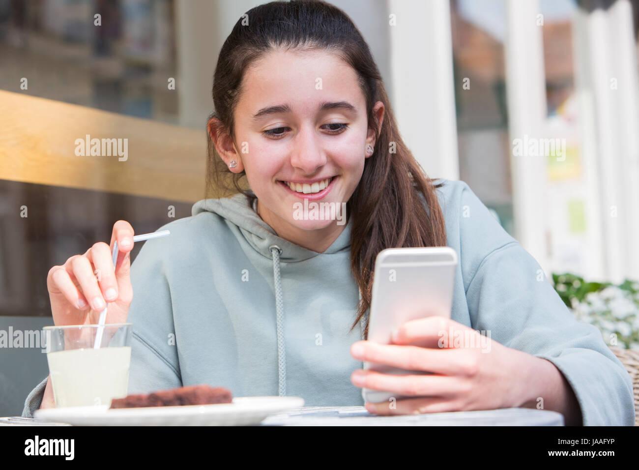 Niña en el Café la lectura de mensajes de texto en el teléfono móvil Imagen De Stock