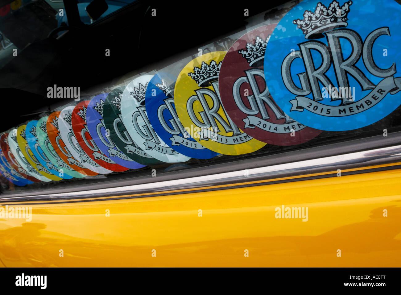 Una colección de pertenencia GRRC pegados a los coches en la ventanilla lateral de un vehículo en Goodwood, Imagen De Stock