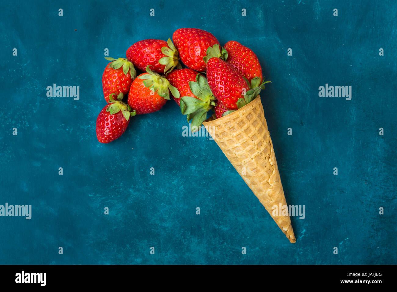 Maduras Fresas orgánicas en barquillo de helado, derramando la ...