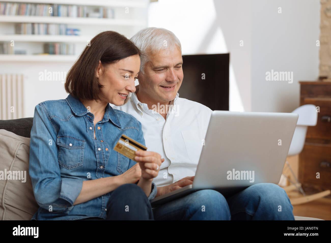 Pareja madura conectado con un ordenador portátil y compras online Imagen De Stock