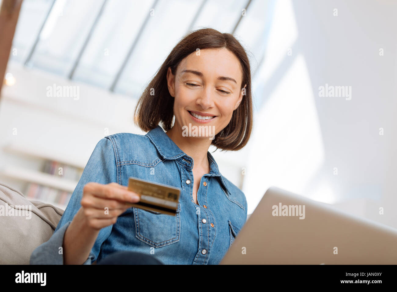 Mujer con un portátil conectado y compras online Imagen De Stock