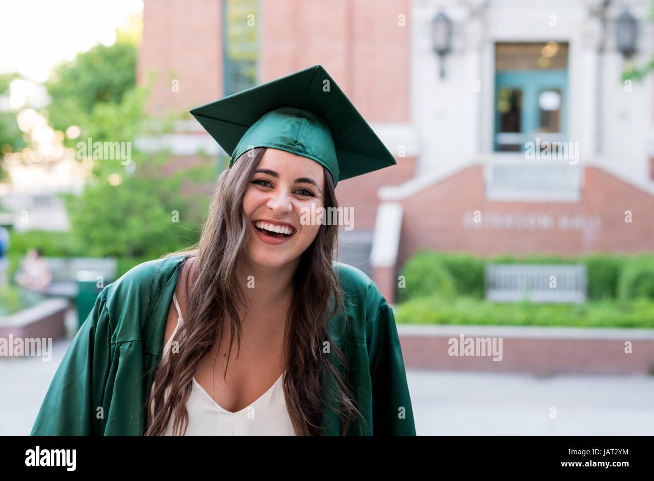 8b6560c97 Chica guapa posando para una foto de graduación en el campus durante su  último año de universidad justo antes de la graduación.