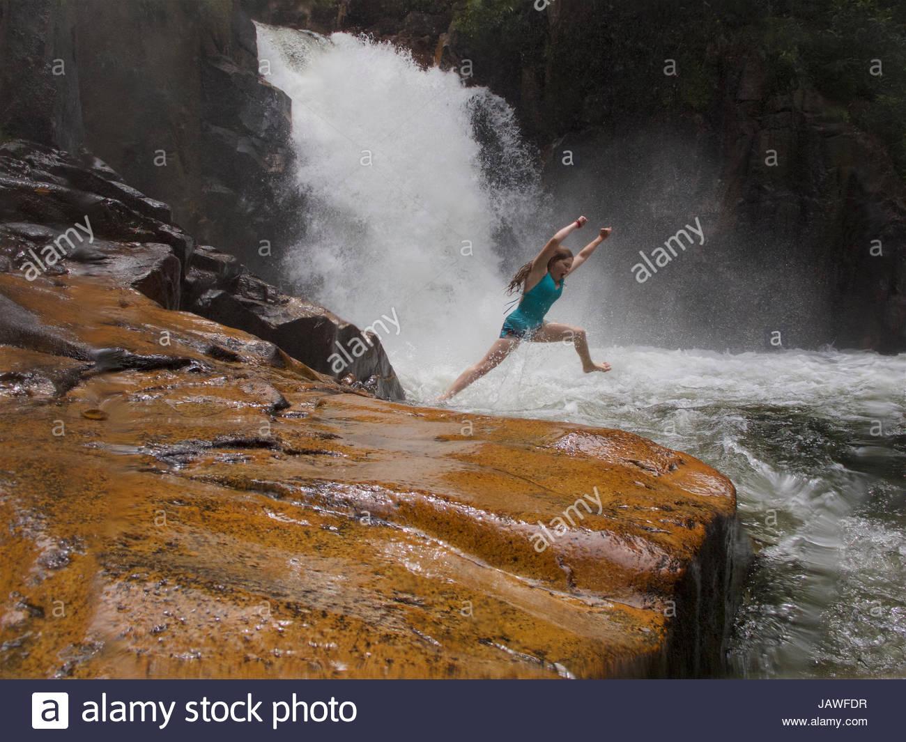 Una niña salta en el agua debajo de Riam Berasap, las caídas de las nieblas, que es la cascada más Imagen De Stock