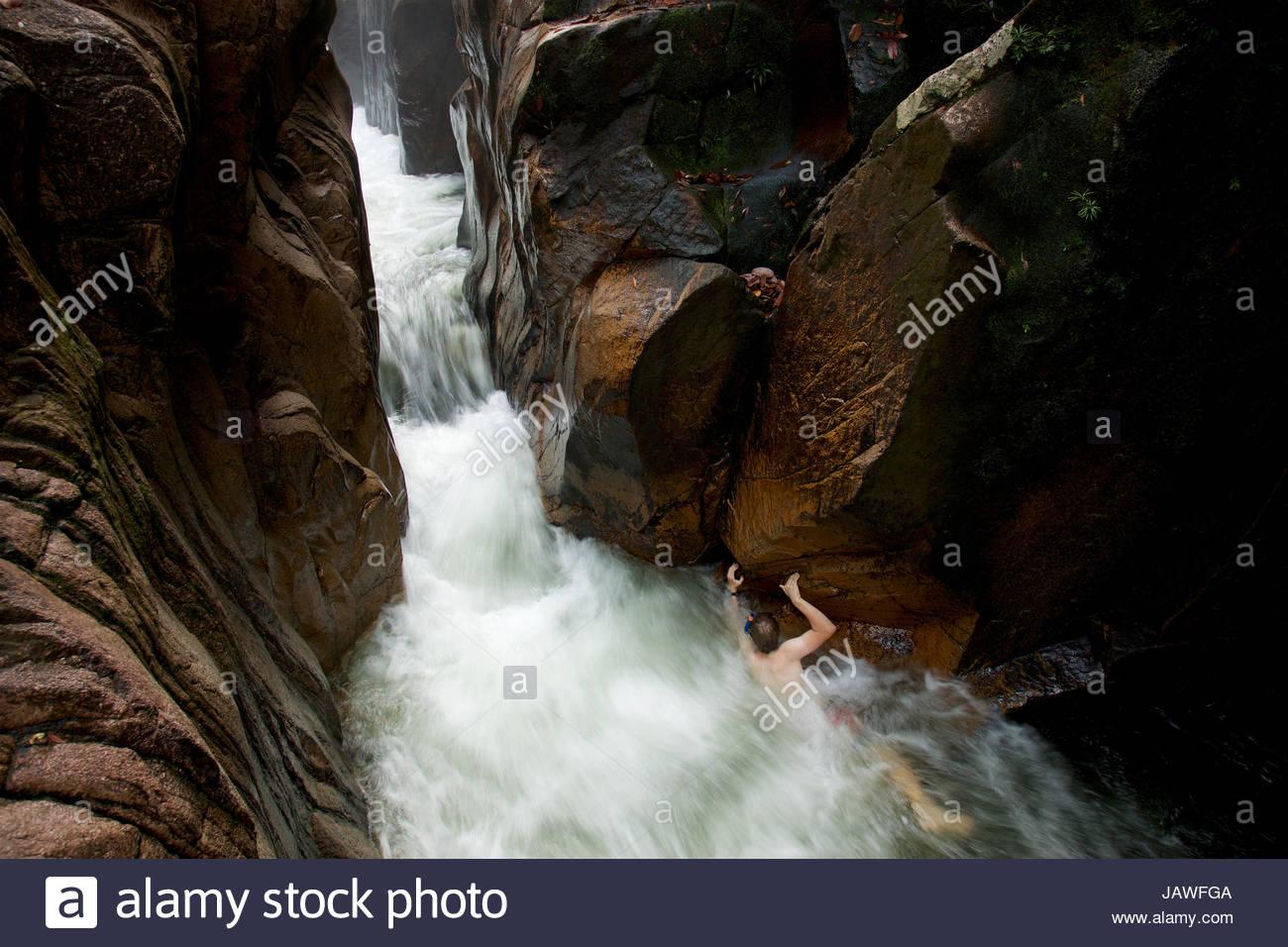 El agua brota a través Riam, o el canal Parit Falls, una inusual la ranura en la parte superior de la cascada Imagen De Stock