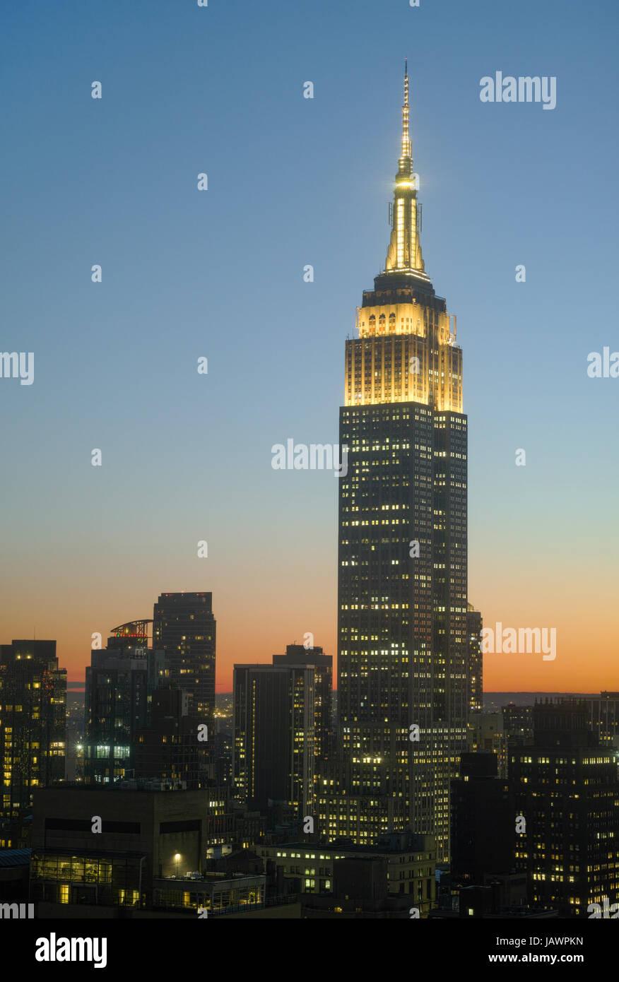 Edificio Empire State al atardecer con las luces de la torre amarilla en honor a los jóvenes artistas y escritores. Oscuras siluetas de edificios cercanos por debajo de ella. - Junio Foto de stock