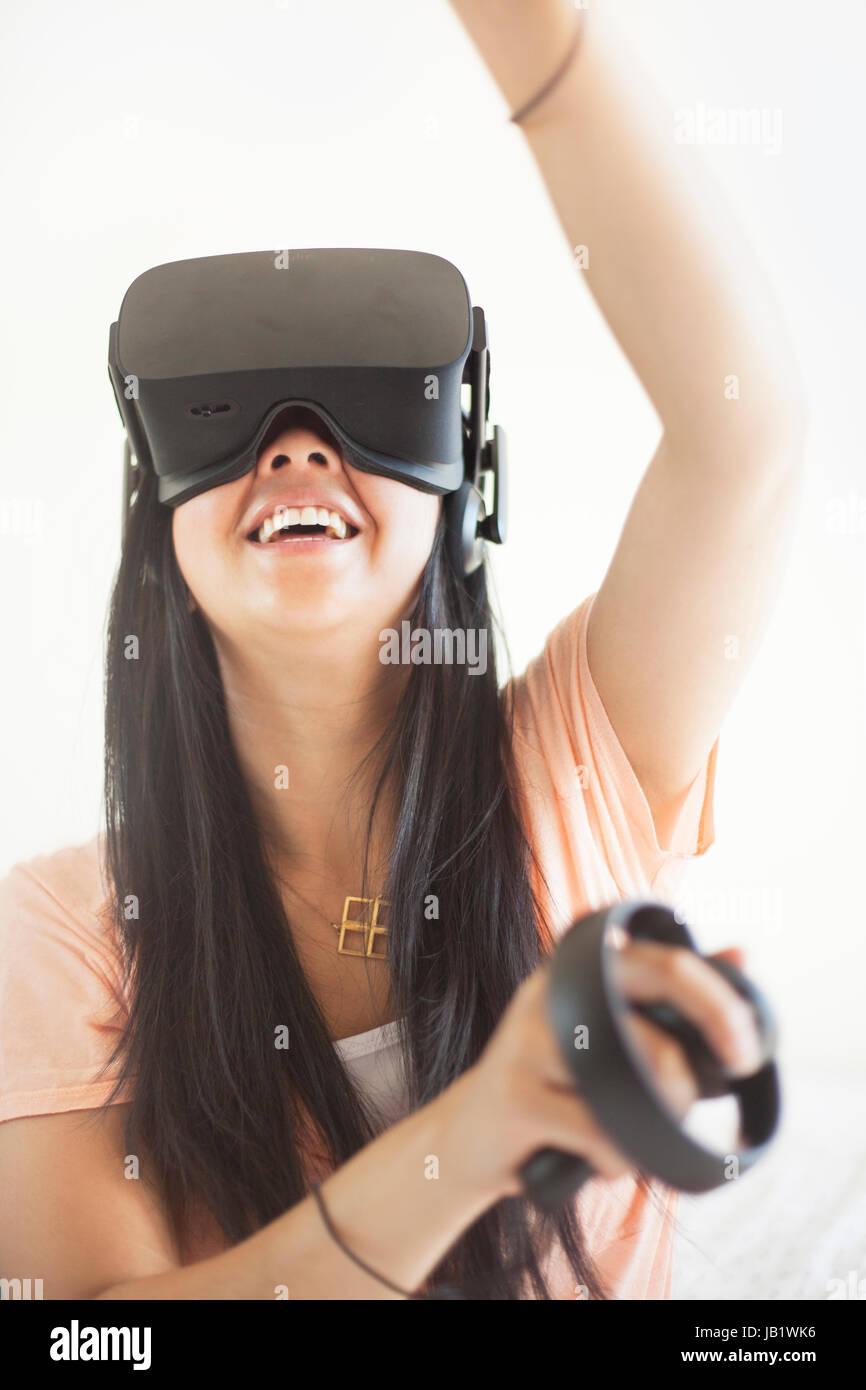 Joven mujer asiática vistiendo casco de realidad virtual oculus rift y demostrar cómo utilizar el control táctil Foto de stock