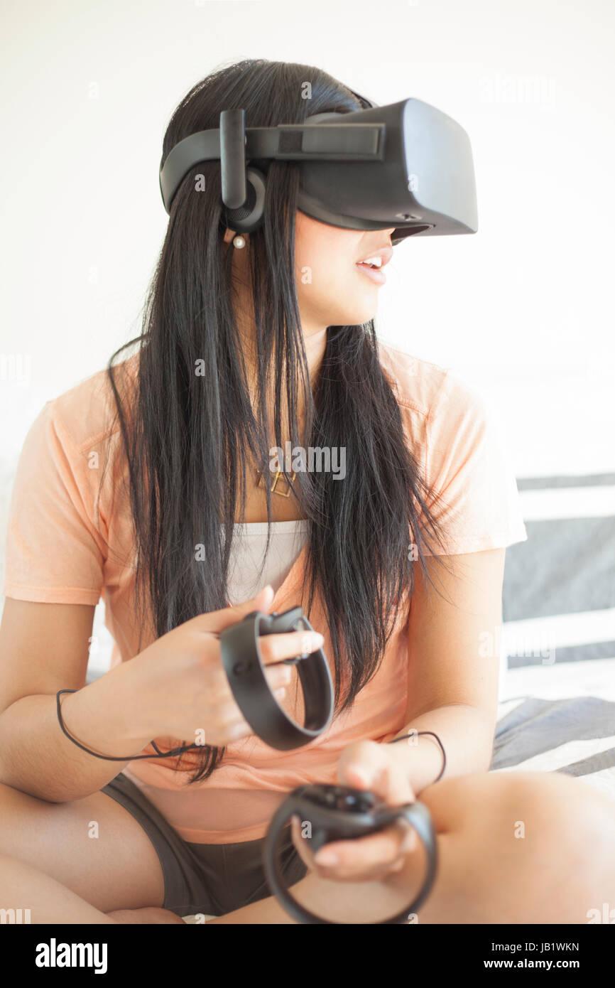 Joven mujer asiática vistiendo casco de realidad virtual oculus rift y demostrar cómo utilizar los controles táctiles Foto de stock