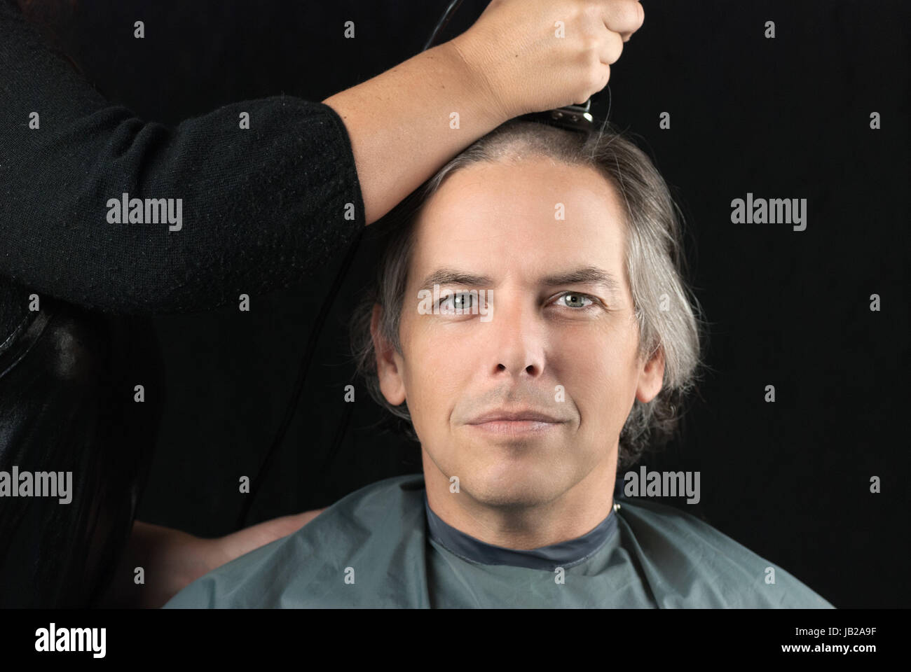 Close-up de una grave hombre mirando a la cámara mientras su largo cabello se rasura de recaudación de fondos para Foto de stock