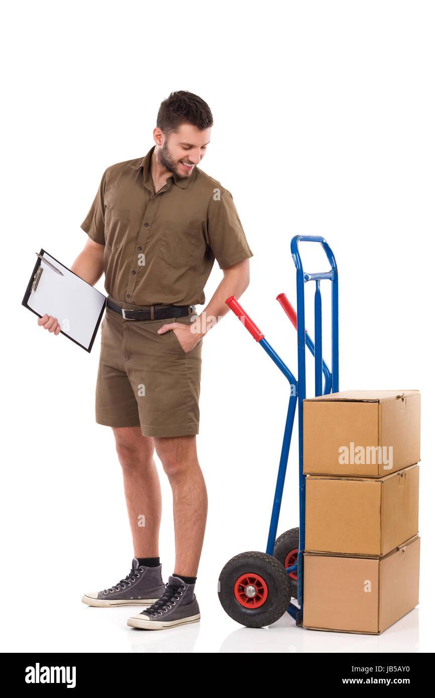 Courier masculina está de pie, sosteniendo el portapapeles y mirando por encima del hombro en empujando el carro Foto de stock