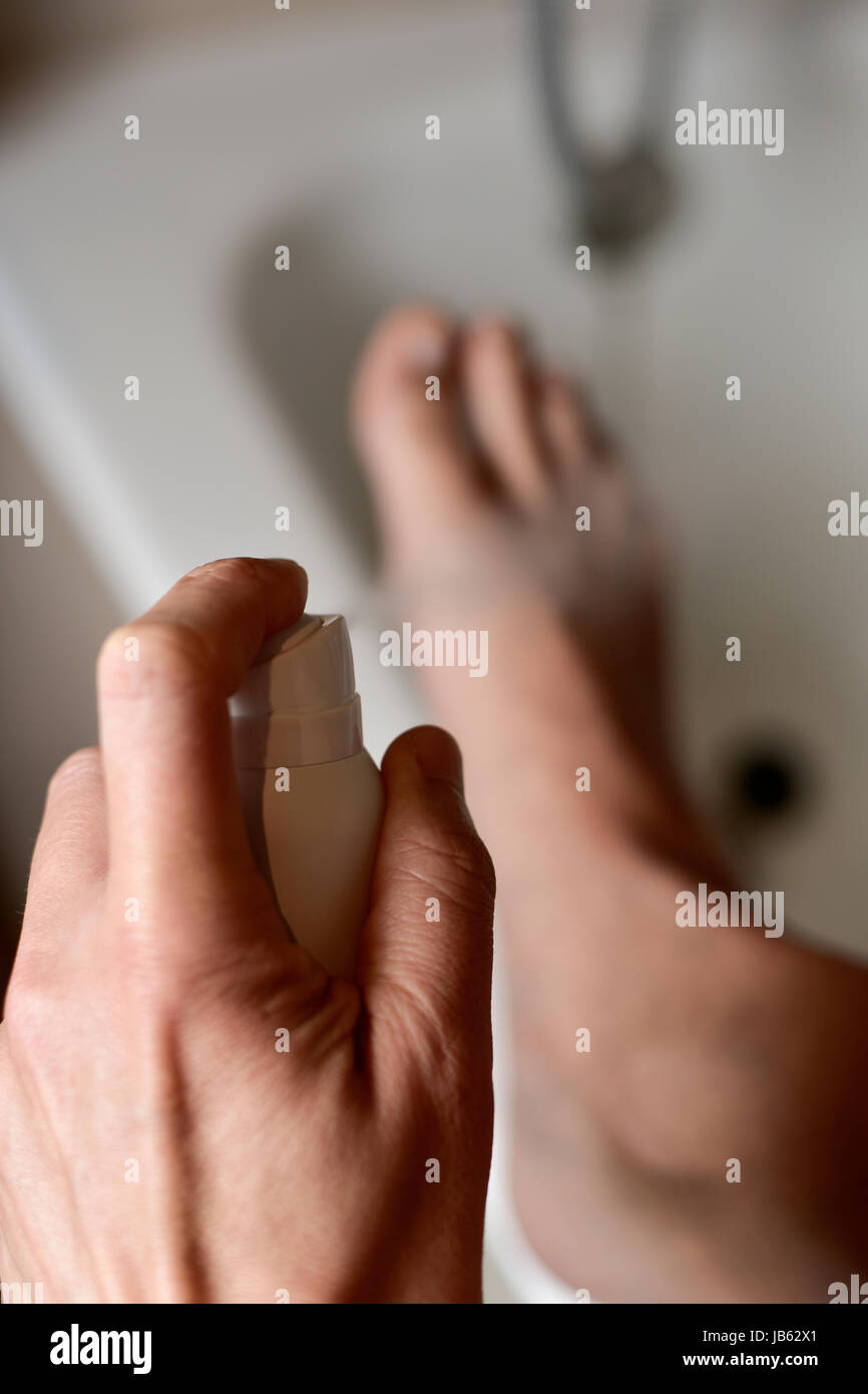 Primer plano de un joven hombre caucásico joven en el baño aplicar desodorante para los pies Imagen De Stock