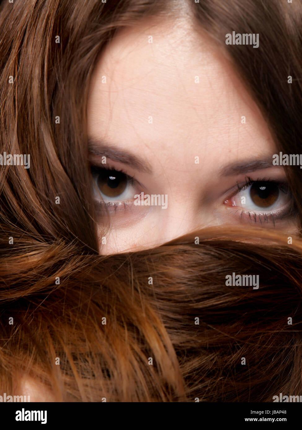Close-up retrato de una bella mujer cubre el rostro por largos pelos marrones Foto de stock