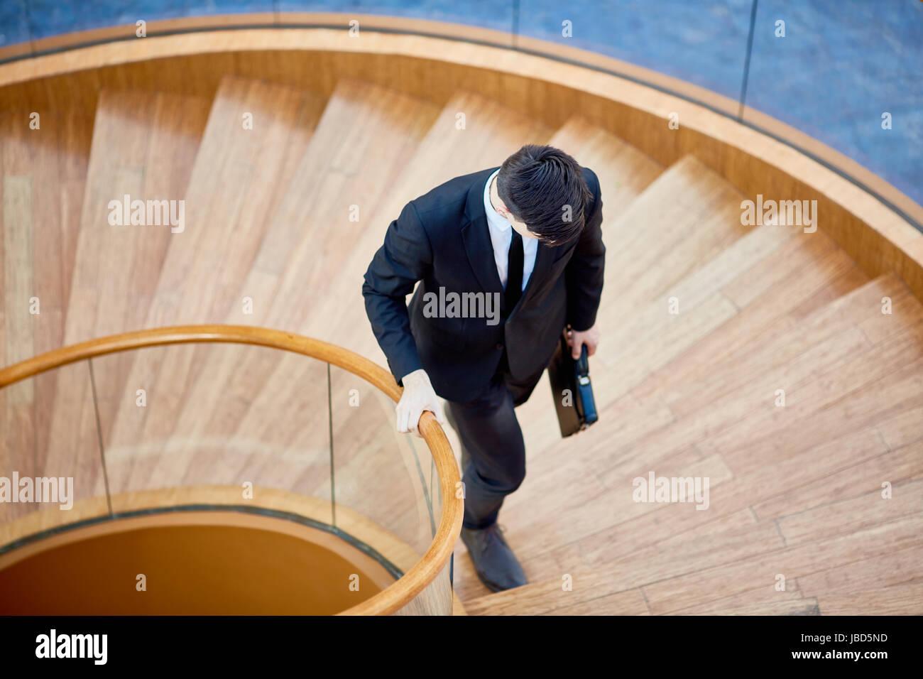 Joven corredor de bolsa con maletín moviendo hacia arriba en la escalera Imagen De Stock