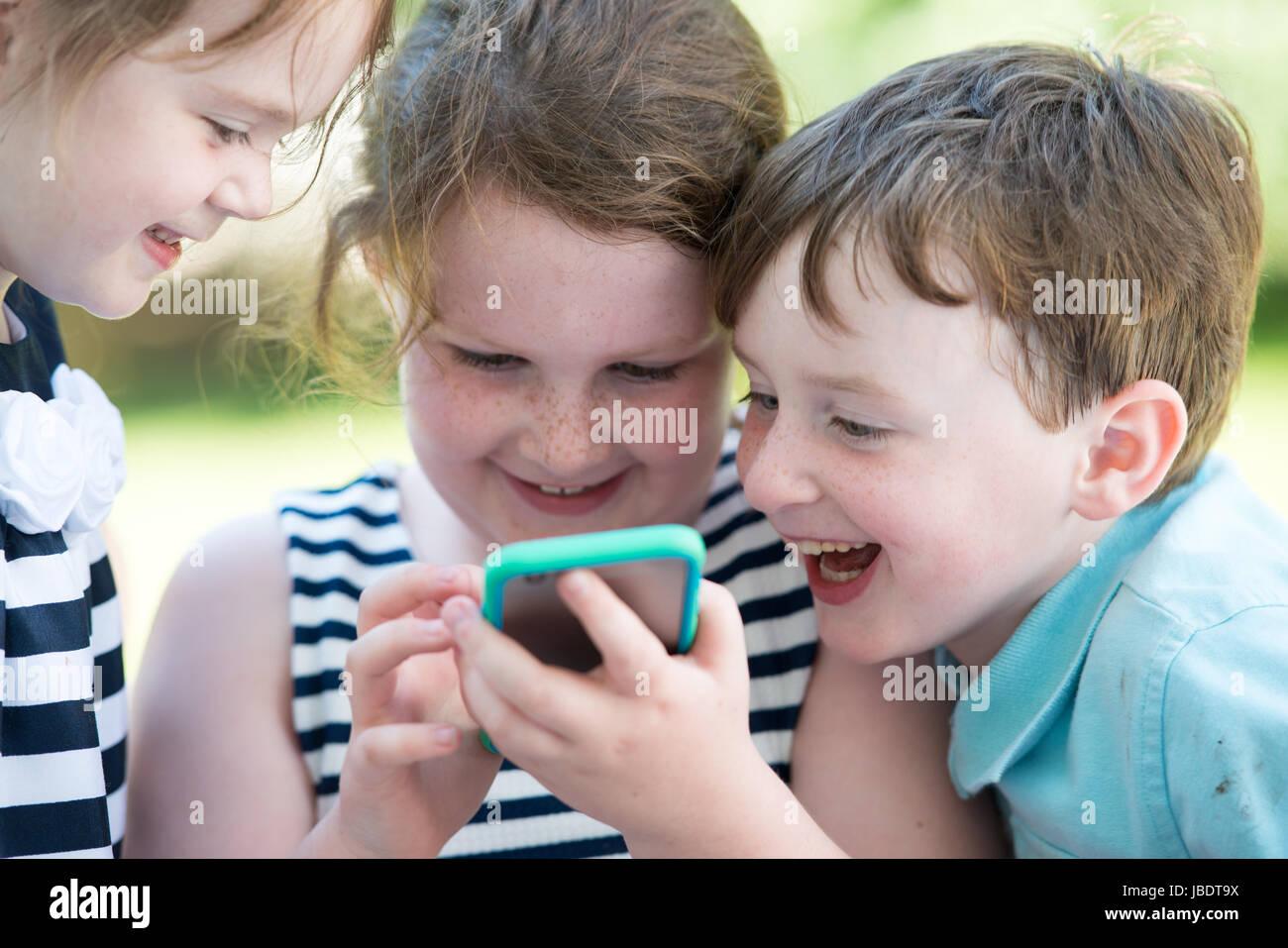 Feliz riendo niños jugando con el smartphone fuera Imagen De Stock