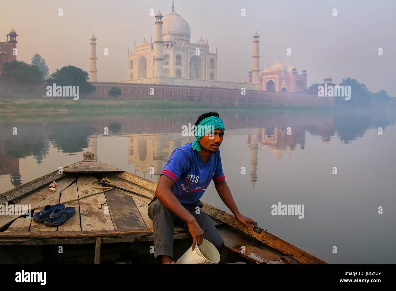 Hombre local achicar agua del barco sobre el río Yamuna cerca del Taj Mahal, en la mañana, Agra, Uttar Imagen De Stock