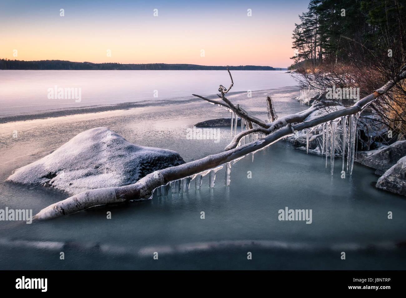 Pintoresco paisaje con carámbanos y lago en la noche de invierno Imagen De Stock