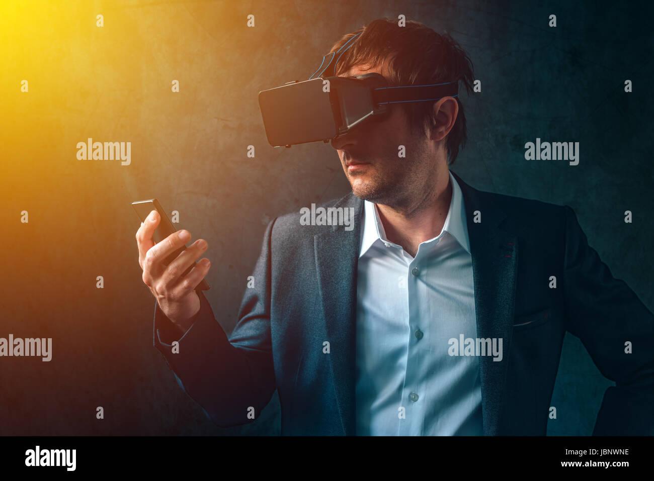 La realidad virtual y tecnología futurista en las empresas modernas, empresario con VR auriculares y smartphone utilizando new tech gadgets para desarrollar y administrar Foto de stock