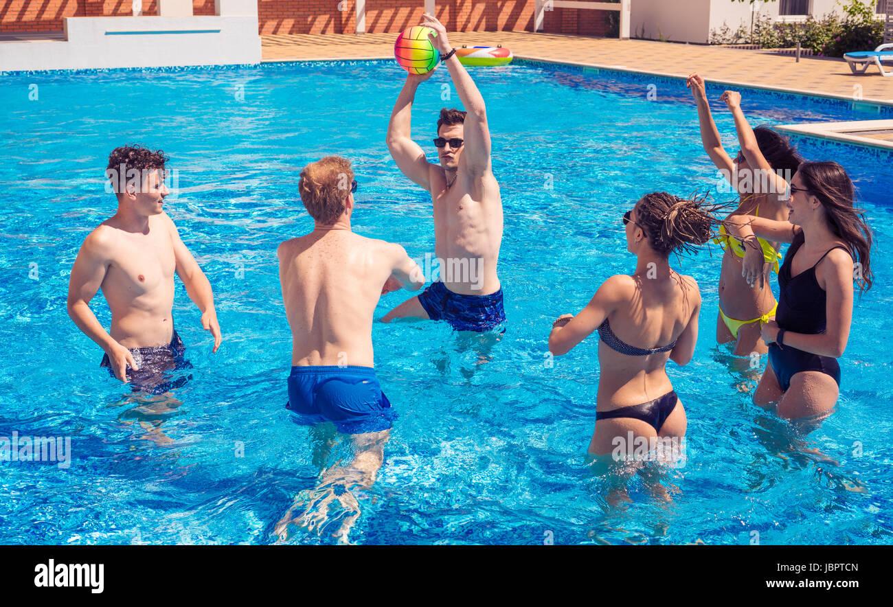Grupo de parejas alegres amigos jugando voleibol acuático. Imagen De Stock